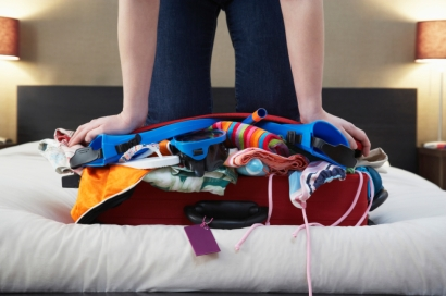 Woman Kneeling On Overstuffed Suitcase